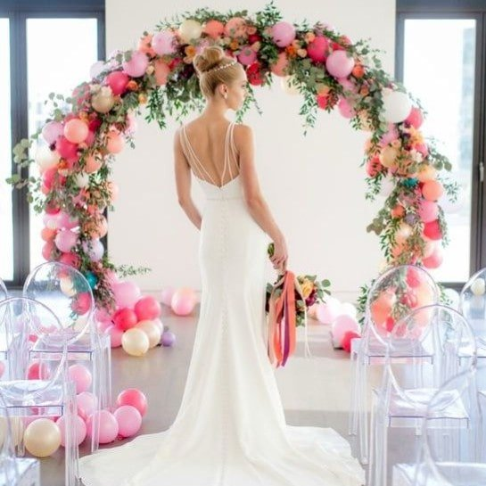bride in front of pink balloon arch