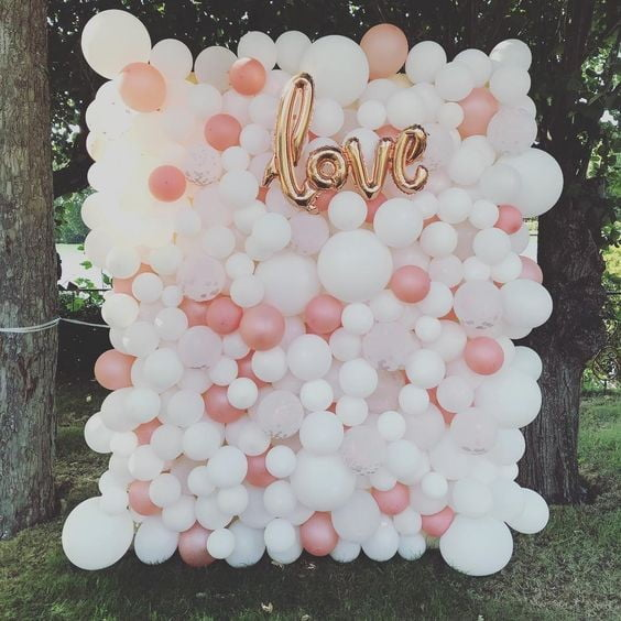 white balloon wall with some pink balloons