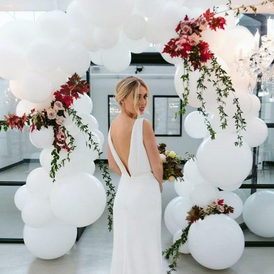 bride in front of white balloon arch