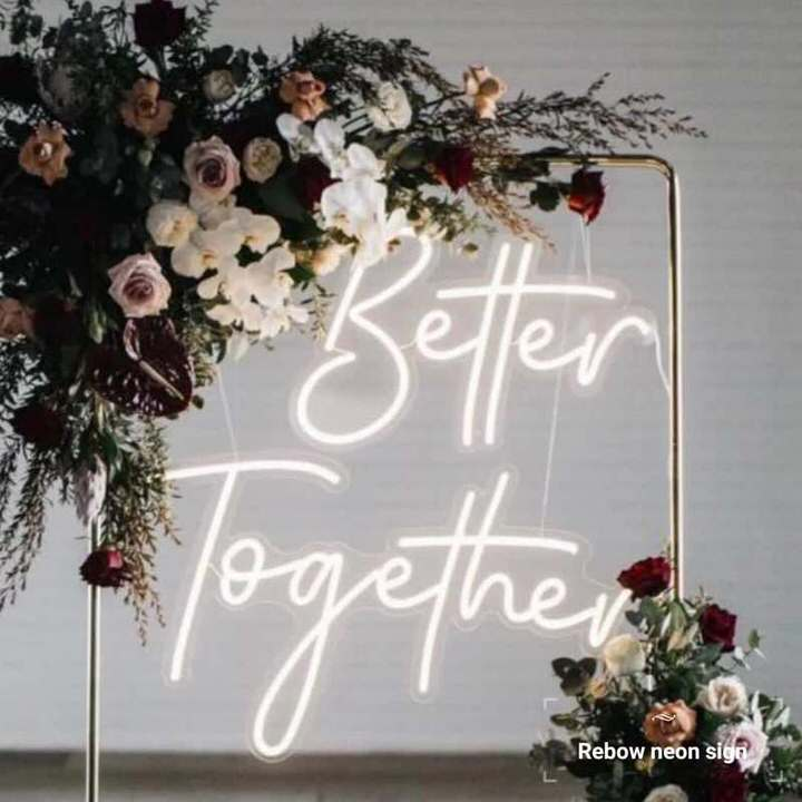 better together neon sign hanging from copper arch