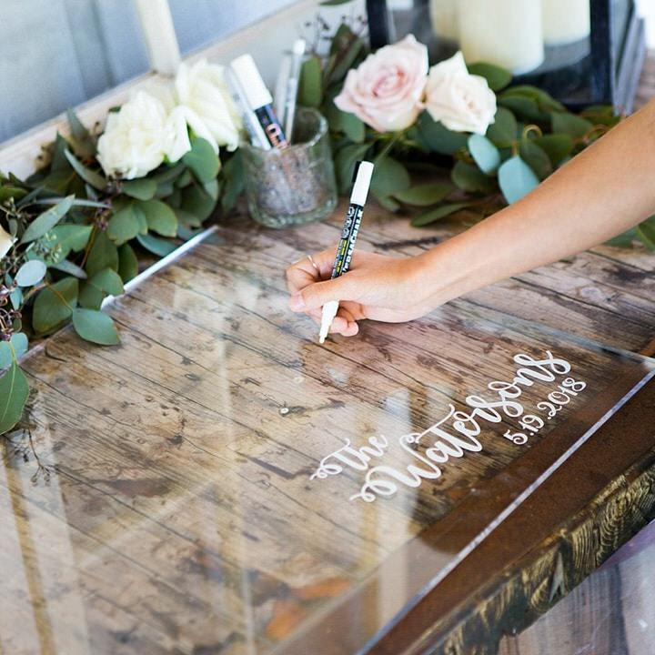 Clear acrylic guest book on table with flowers