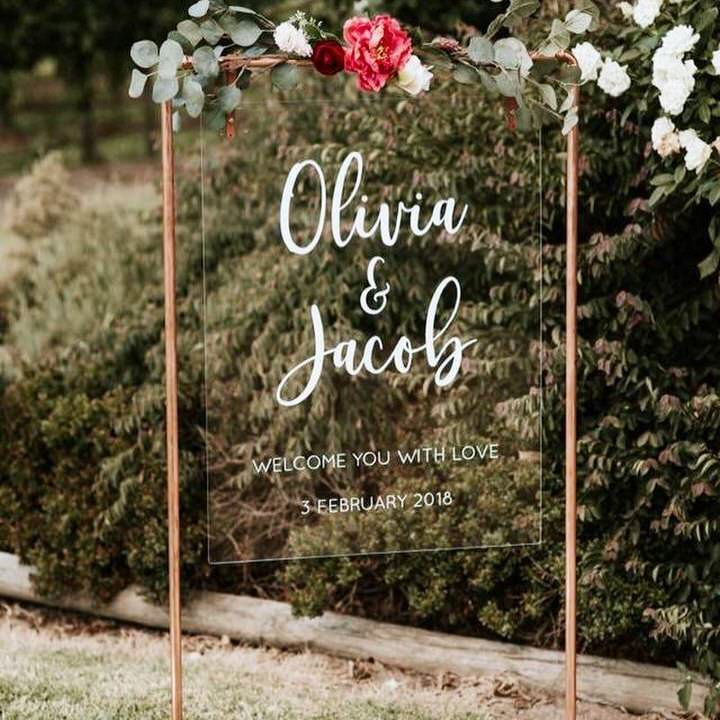 Clear Acrylic Welcome Sign Oliva and Jacob hanging from copper pipe frame