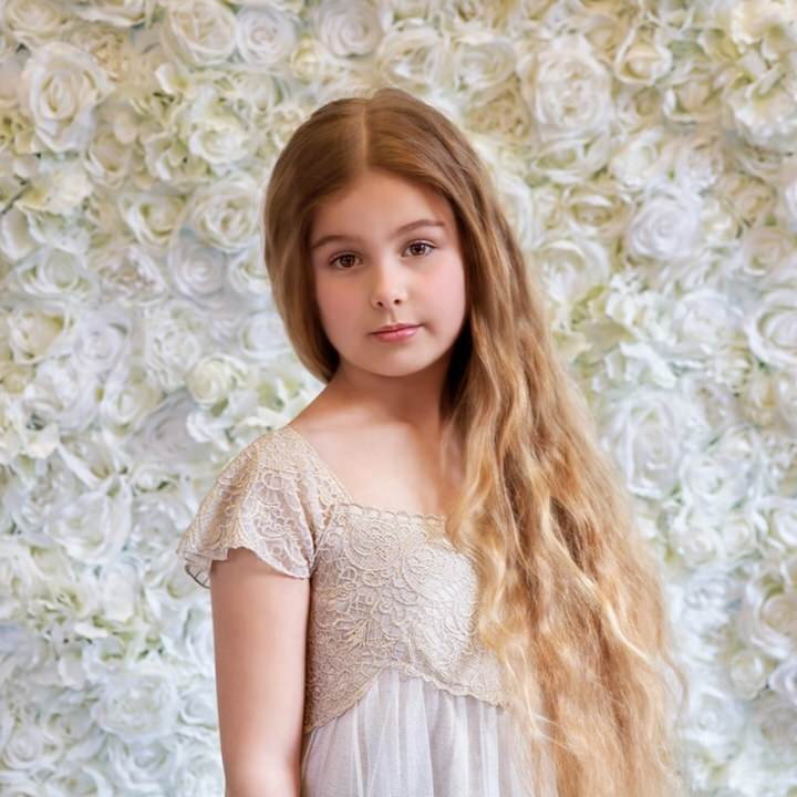 Girl standing in front of white flower wall
