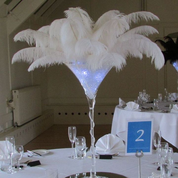 Martini glass centrepiece with white feathers on table 2