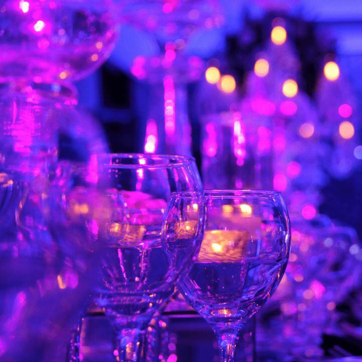 2 wine glasses with pink purple lighting