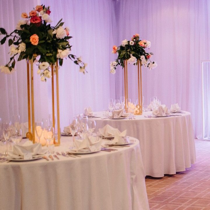 2 Floral Stands on tables with orange and white flowers