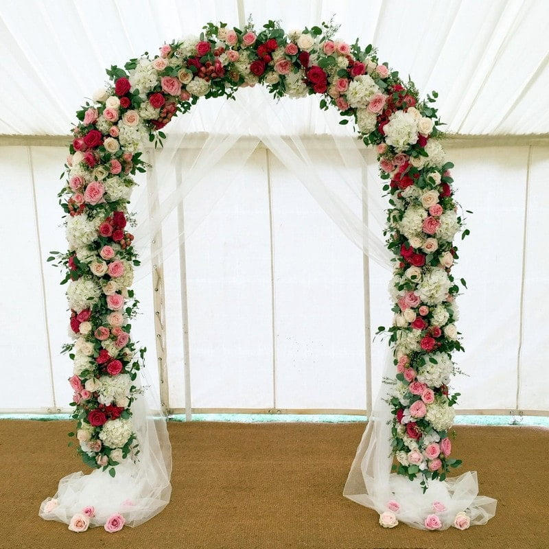 red, pink, white & green Flower Arch in tent