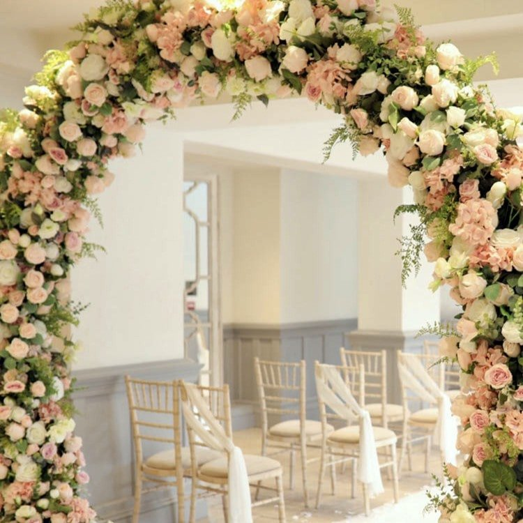 wedding flower arch and white chairs