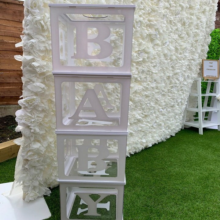 White baby blocks in front of white Flower Wall