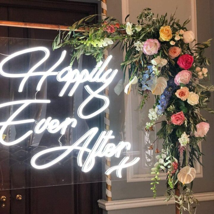 Happily Ever After sign on copper pipe frame with yellow,pink.blue,peach & cream flowers