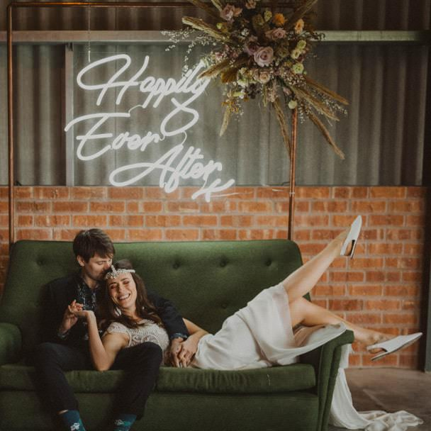 Happily Ever After sign with wedding couple on green couch