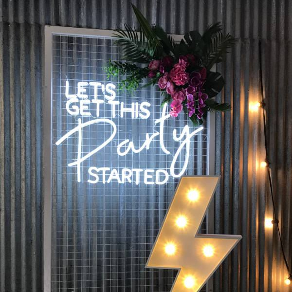 Lets Get This Party Started sign on metal frame with pink flowers and cream electricity bolt