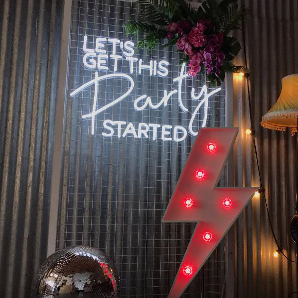 Lets Get This Party Started sign on metal frame with pink flowers & red electricity bolt