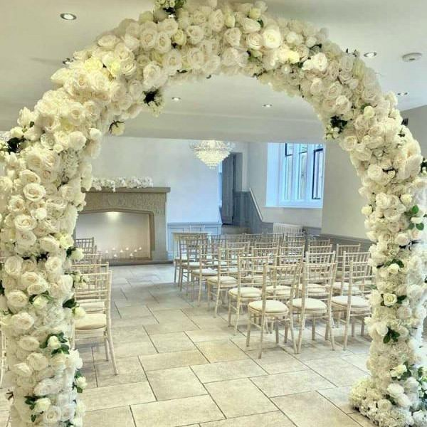 White flower Moon Gate Arch in room with chairs