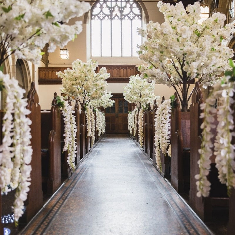 Wedding church aisle with flowers on pews