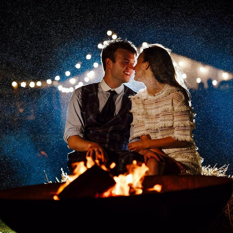 kissing couple behind fire outdoors