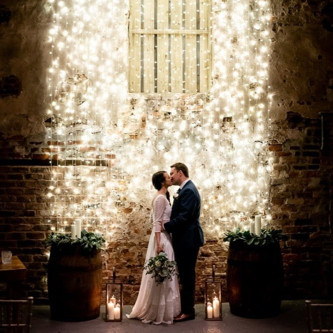 bride and groom in front of brightly lit wall