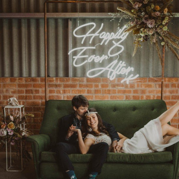 bride and groom on couch in front of happily ever after neon sign