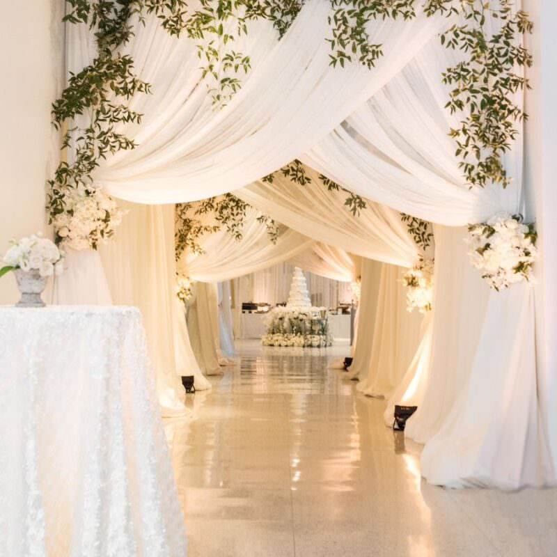 multiple white draping curtains leading to cake