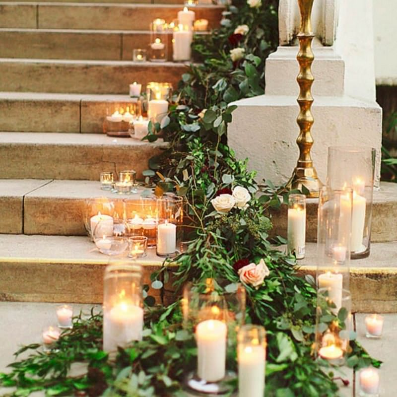 staircase with candles and greenery
