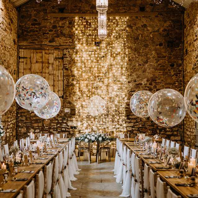 brick room with string lights & confetti ballons on tables