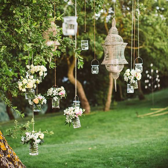 lantern, candles & flower vases hanging from tree branch