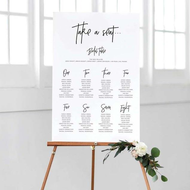 White Take a Seat Table Plan on wooden easel