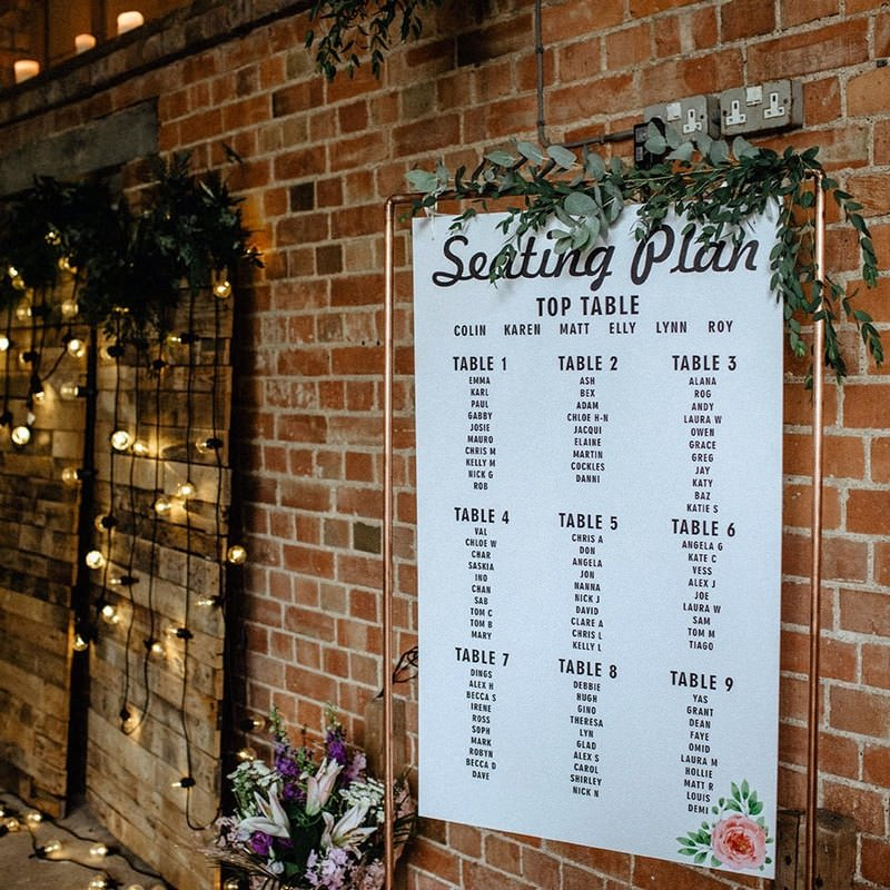 White seating plan on copper pipe frame beside brick wall