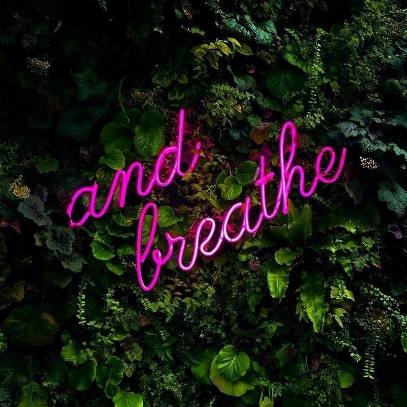 and breathe purple neon sign