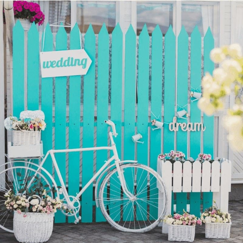 aqua fence with wedding sign behind bike in front