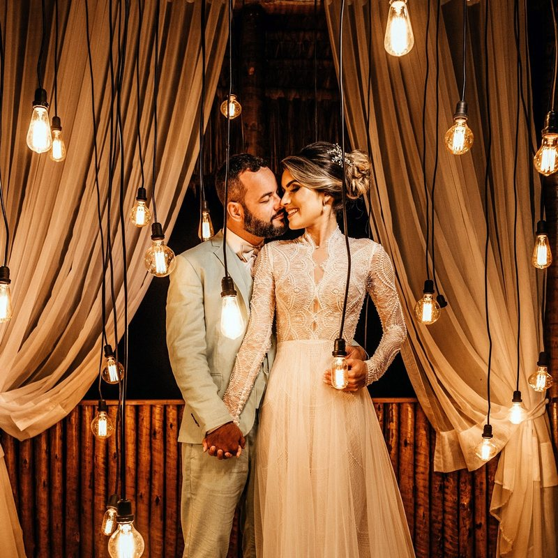 bride and groom in front of hanging light